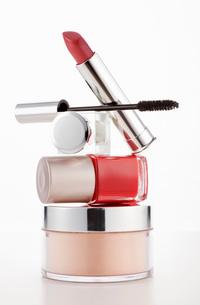 Lipstick, mascara and fingernail polish stacked on moisturizの写真素材 [FYI02144624]