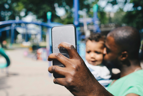 Father taking selfie through smart phone while kissing son at parkの写真素材 [FYI02144661]