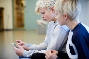 Boy looking at friend using mobile phone in school corridorの写真素材 [FYI02144709]
