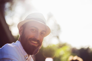 Low angle portrait of happy man wearing fedora on sunny dayの写真素材 [FYI02144743]