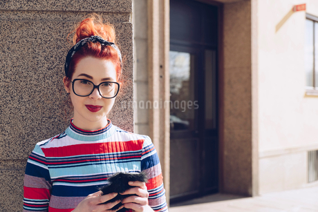 Portrait of young female hipster holding mobile phone while standing against wallの写真素材 [FYI02144752]