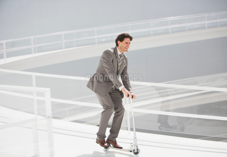 Businessman riding scooter down walkwayの写真素材 [FYI02144754]