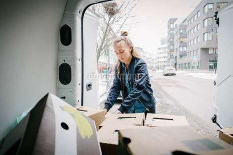 Female worker removing cardboard box from delivery vanの写真素材 [FYI02144777]