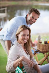 Portrait of smiling couple enjoying picnic at lakesideの写真素材 [FYI02144812]