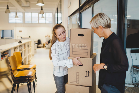 Mature businesswoman looking at female colleague carrying cardboard boxes in new officeの写真素材 [FYI02144820]