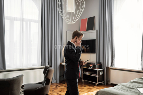 Side view of businessman talking on mobile phone while standing in hotel roomの写真素材 [FYI02144824]