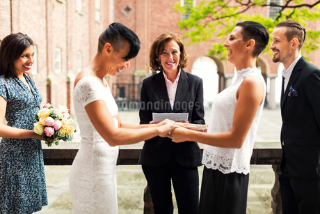 Priest and guests looking at cheerful lesbian couple holding handsの写真素材 [FYI02144865]