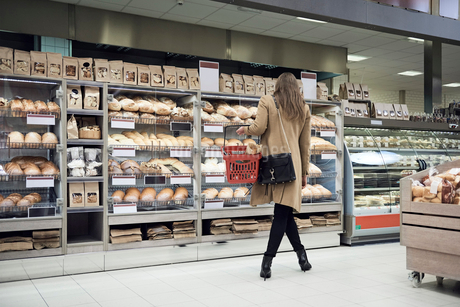 Rear view of woman standing by breads in rack at supermarketの写真素材 [FYI02144920]