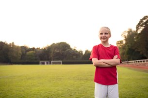 Happy athlete looking away standing with arms crossed on soccer field against skyの写真素材 [FYI02144993]