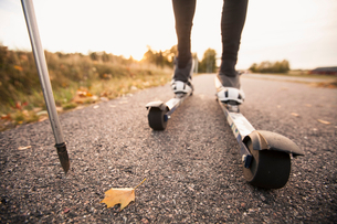 Low section of man roller skiing on country roadの写真素材 [FYI02145001]
