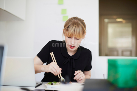 Mid adult businesswoman eating lunch at table in officeの写真素材 [FYI02145094]