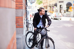 Businessman with bicycle on street in city during sunny dayの写真素材 [FYI02145111]