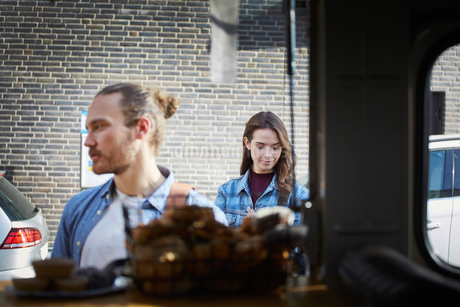 Young man and woman standing at food truck in cityの写真素材 [FYI02145181]