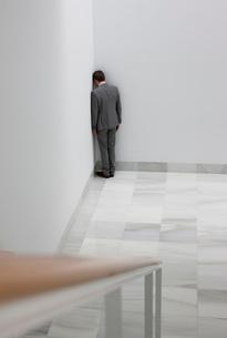 Dejected businessman standing in cornerの写真素材 [FYI02145240]