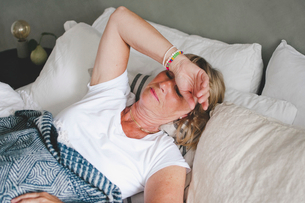 Senior woman suffering from cold lying on bed at homeの写真素材 [FYI02145305]
