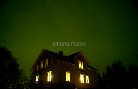 Low angle view of green sky over illuminated houseの写真素材 [FYI02145313]