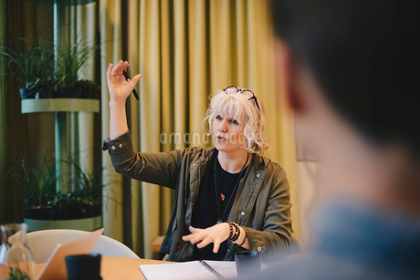 Confident businesswoman explaining strategy while sitting at conference tableの写真素材 [FYI02145332]