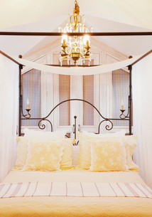 Chandelier over four poster bed with yellow linensの写真素材 [FYI02145428]