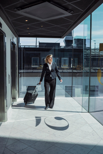 Mature businesswoman pulling wheeled luggage in hotel corridorの写真素材 [FYI02145441]