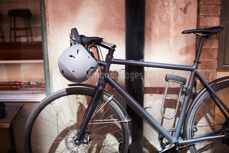 Bicycle with helmet parked against wall at cityの写真素材 [FYI02145473]