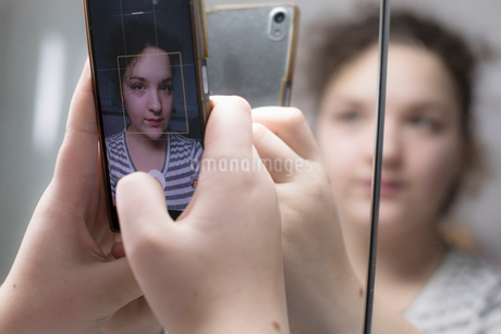 Cropped image of girl taking selfie through smart phone in bathroomの写真素材 [FYI02145588]