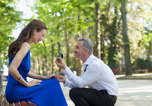 Man with engagement ring proposing to girlfriend in parkの写真素材 [FYI02145699]