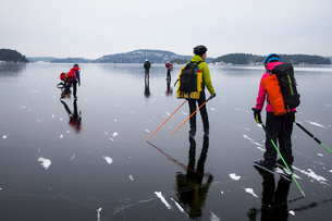 People ice skating on frozen lake against skyの写真素材 [FYI02145714]