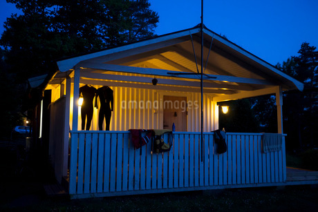 Diving suits and life jackets are drying in illuminated log cabin in forest at duskの写真素材 [FYI02145735]