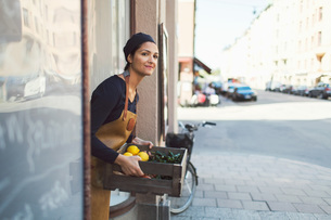 Smiling female owner carrying vegetable crate at entrance of grocery storeの写真素材 [FYI02145739]