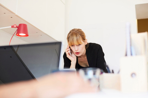 Mid adult businesswoman talking on mobile phone in officeの写真素材 [FYI02145752]