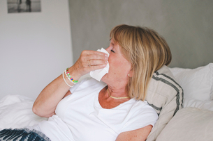 Sick senior woman blowing nose while lying on bed at homeの写真素材 [FYI02145762]