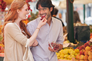 Smiling couple tasting fruit in marketの写真素材 [FYI02145821]