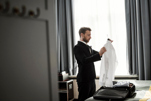 Side view of businessman holding white shirt in coathanger at hotel roomの写真素材 [FYI02145839]