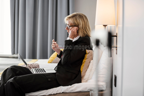 Side view of businesswoman adjusting headphones using laptop on bed at hotel roomの写真素材 [FYI02145961]