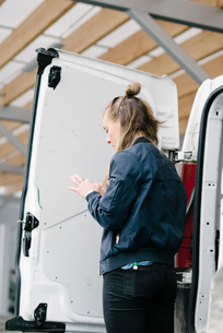 Rear view of female worker using mobile phone by delivery vanの写真素材 [FYI02145987]
