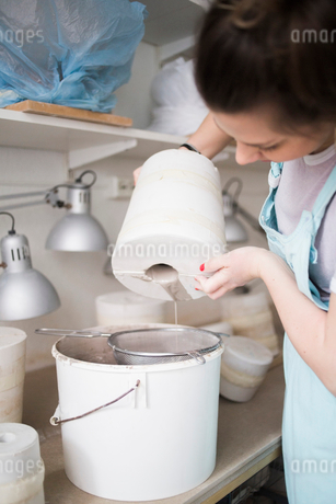 Young female potter pouring clay from vase in colander over bucket at workshopの写真素材 [FYI02145990]