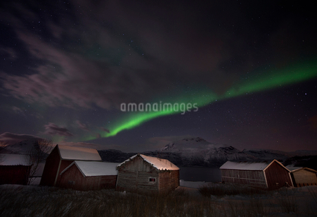 Scenic view of aurora borealis over houses at nightの写真素材 [FYI02145993]