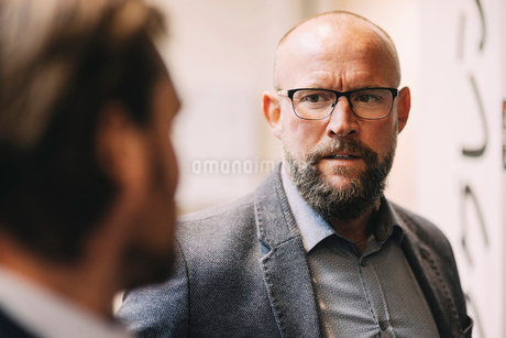 Close-up of businessman discussing with colleague at officeの写真素材 [FYI02146025]