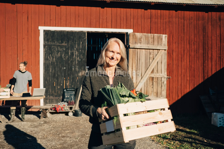 Portrait of smiling mature woman carrying crate full of vegetables with barn in backgroundの写真素材 [FYI02146050]