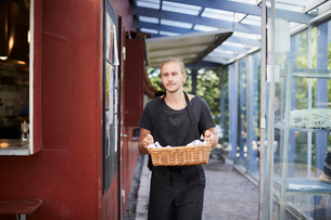 Mid adult waiter carrying basket at cafeの写真素材 [FYI02146053]