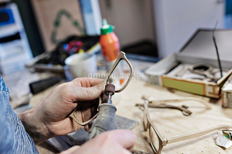 Cropped image of owner making eyeglasses with work tool at workshopの写真素材 [FYI02146072]