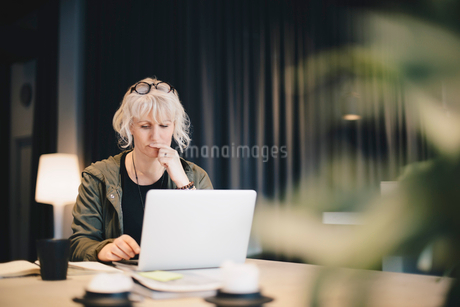 Thoughtful businesswoman using laptop at desk in officeの写真素材 [FYI02146077]