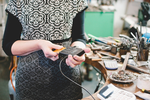 Midsection of senior craftsperson using credit card reader in jewelry workshopの写真素材 [FYI02146084]