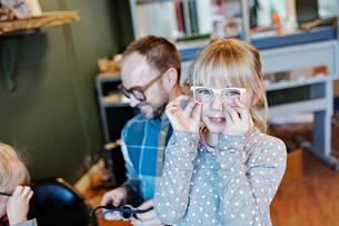 Portrait of girl wearing eyeglasses with family in workshopの写真素材 [FYI02146092]