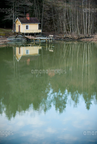 House by calm lake in forestの写真素材 [FYI02146095]