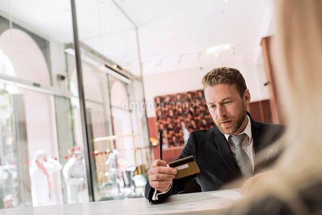 Businessman looking at credit card in hotel receptionの写真素材 [FYI02146101]