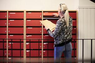 Rear view of teacher taking files from locker in school corridorの写真素材 [FYI02146138]