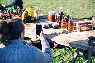 Rear view of mid adult farmers photographing food and drink on tabletの写真素材 [FYI02146190]