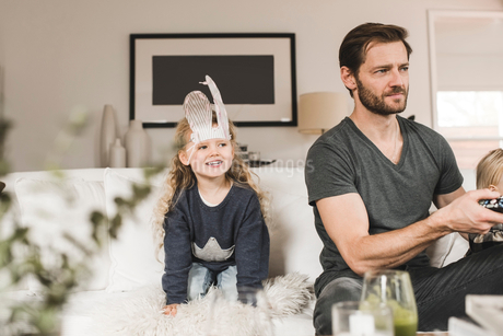 Happy girl with father and sister on sofa watching TV at homeの写真素材 [FYI02146270]