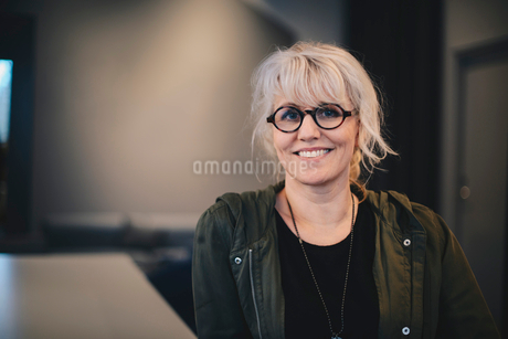 Portrait of happy businesswoman wearing eyeglasses in officeの写真素材 [FYI02146292]